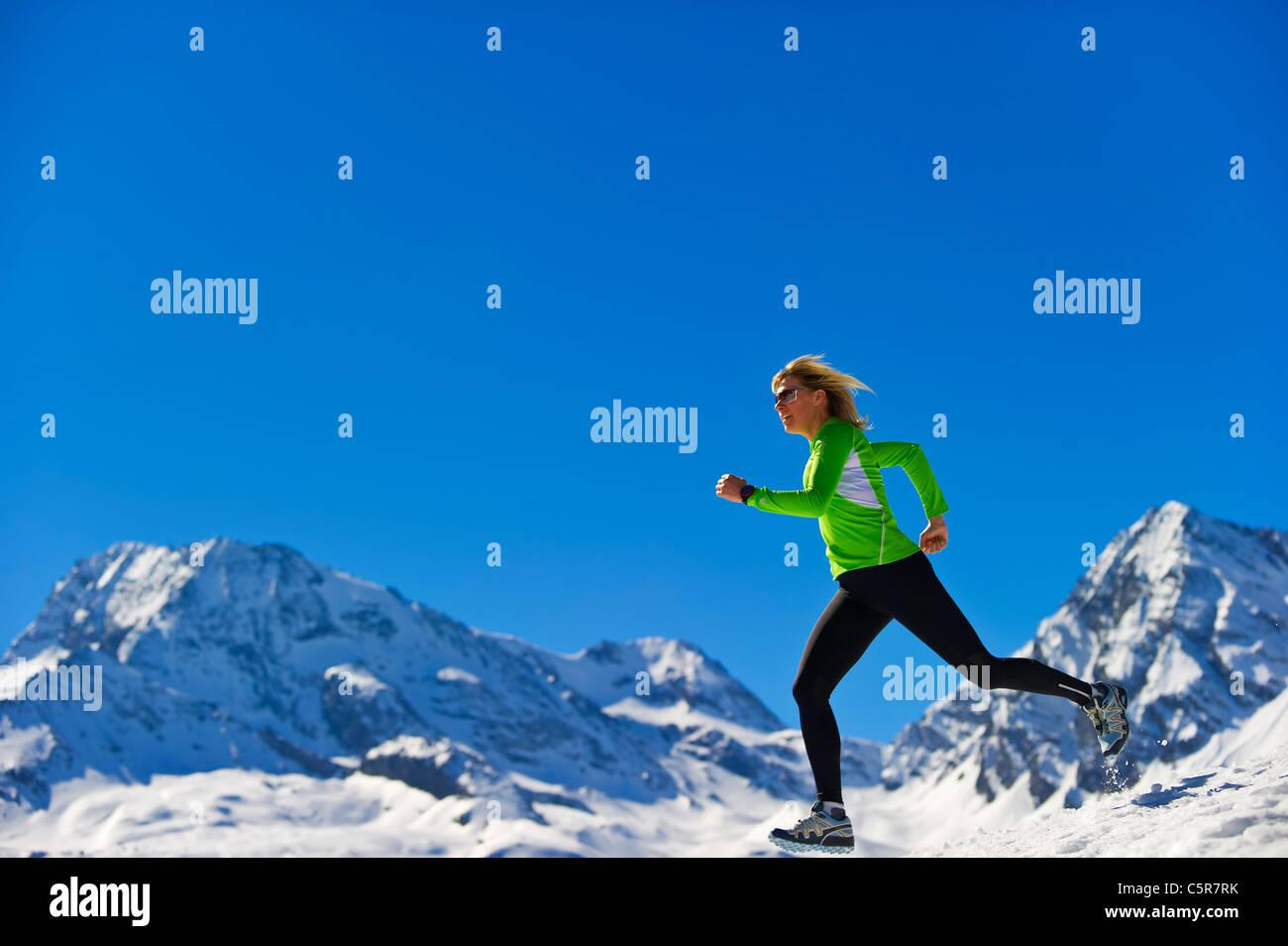 Eine Frau, die schnell über schneebedeckte Berge Joggen. Stockbild