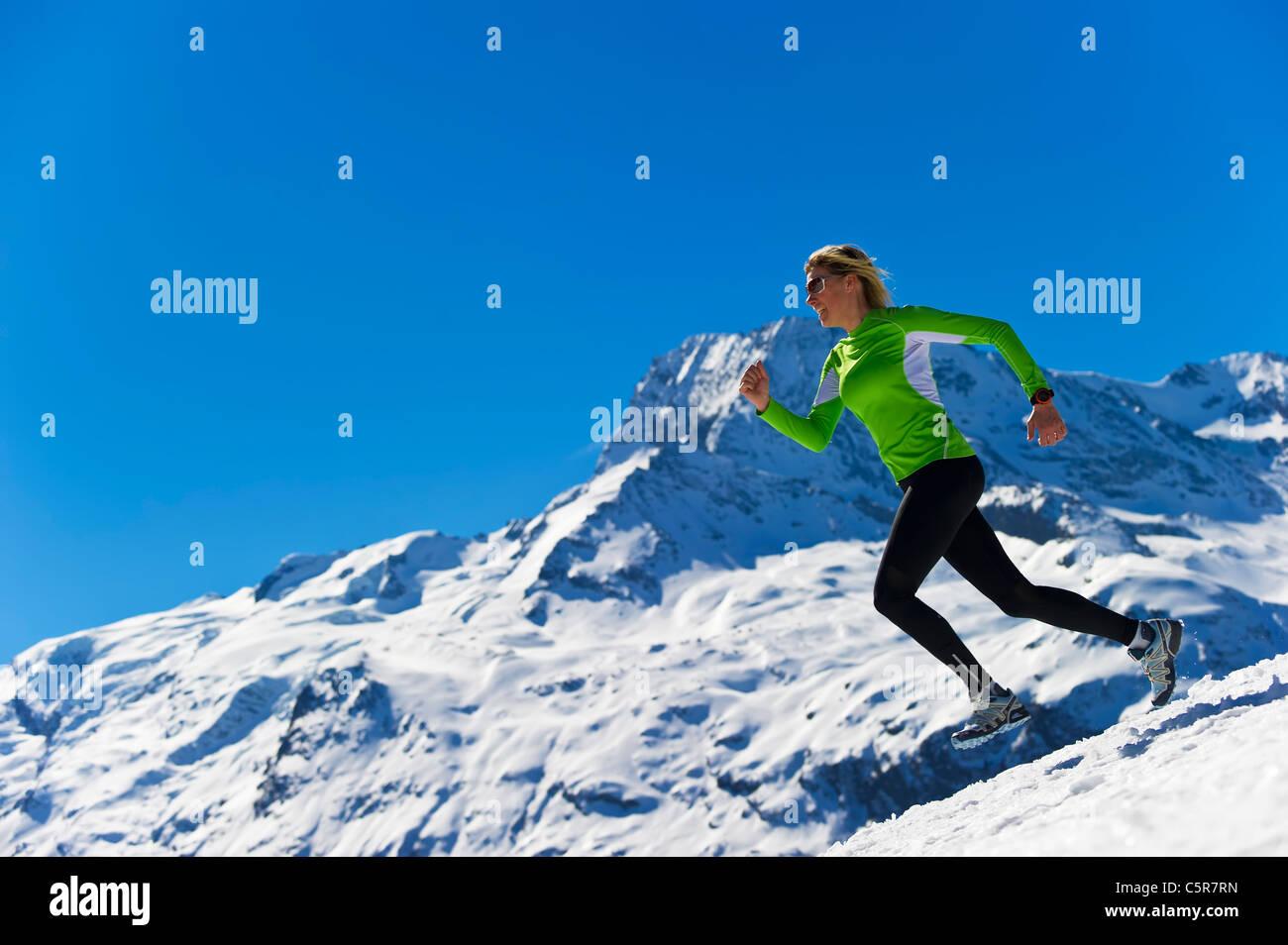 Eine Frau, Joggen im verschneiten alpinen Hochgebirge. Stockbild