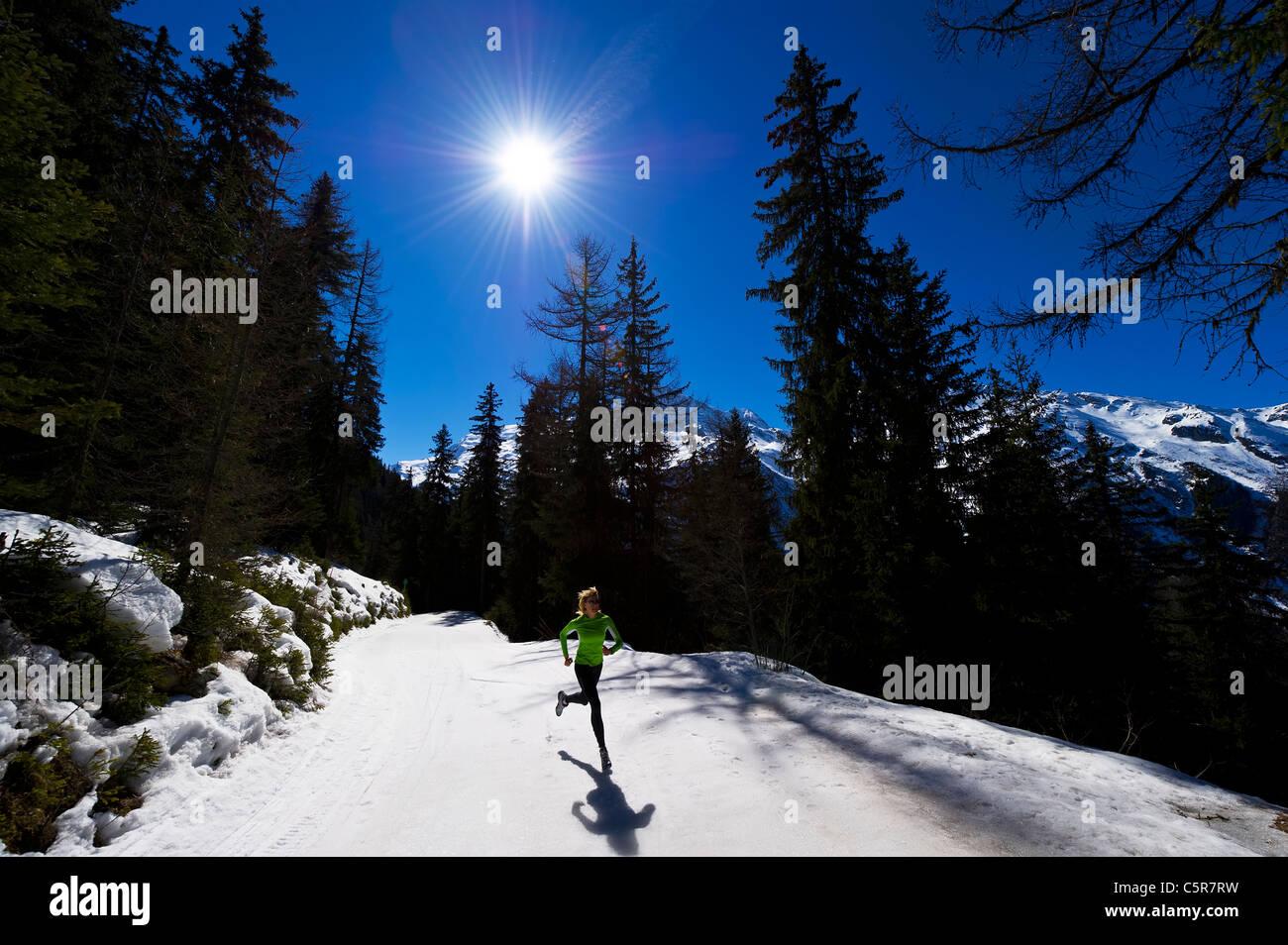 Ein Jogger läuft auf verschneiten Bergen. Stockbild