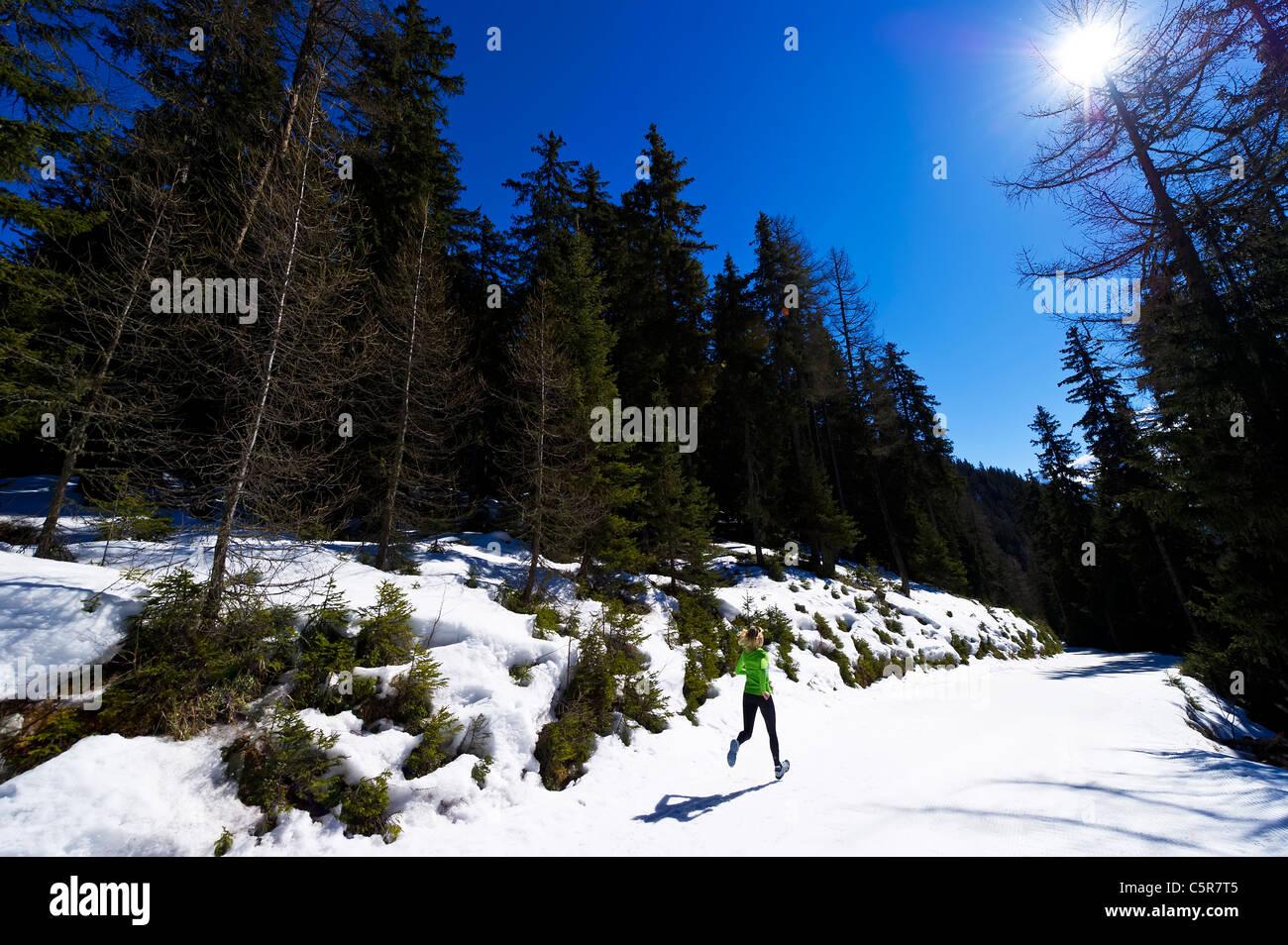 Eine Frau, die durch einen verschneiten Wald joggen. Stockbild