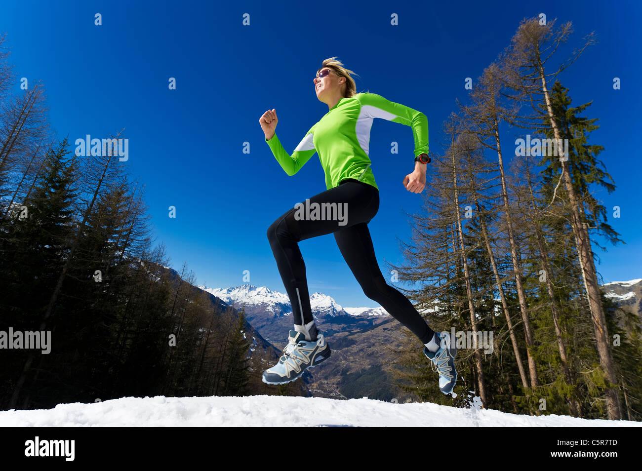 Eine Frau, Joggen durch die verschneiten Berge. Stockbild