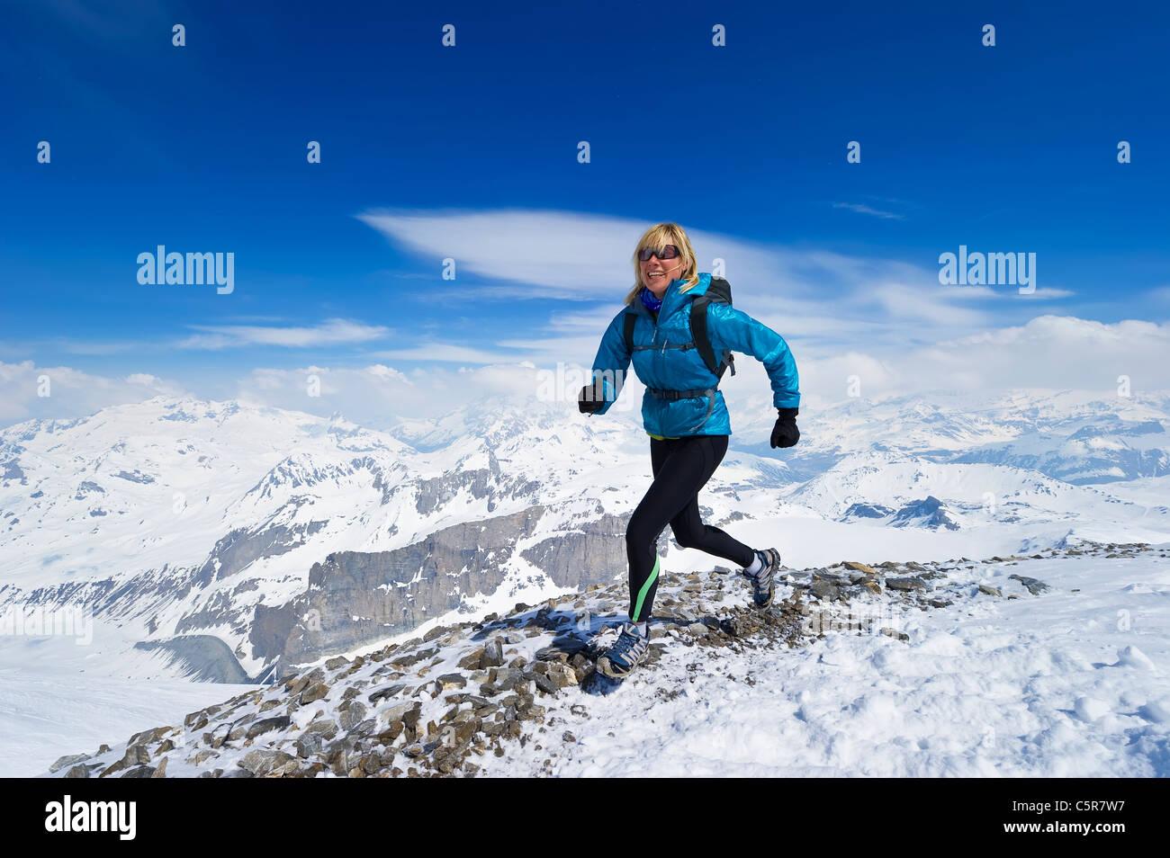 Frauen genießen einen Lauf über einen verschneiten alpinen Gebirge. Stockbild