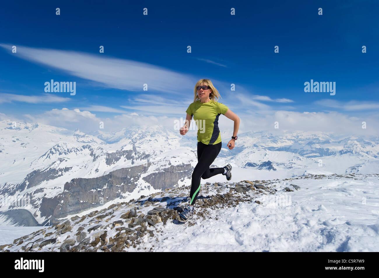 Frau Joggen über verschneite Berge. Stockbild
