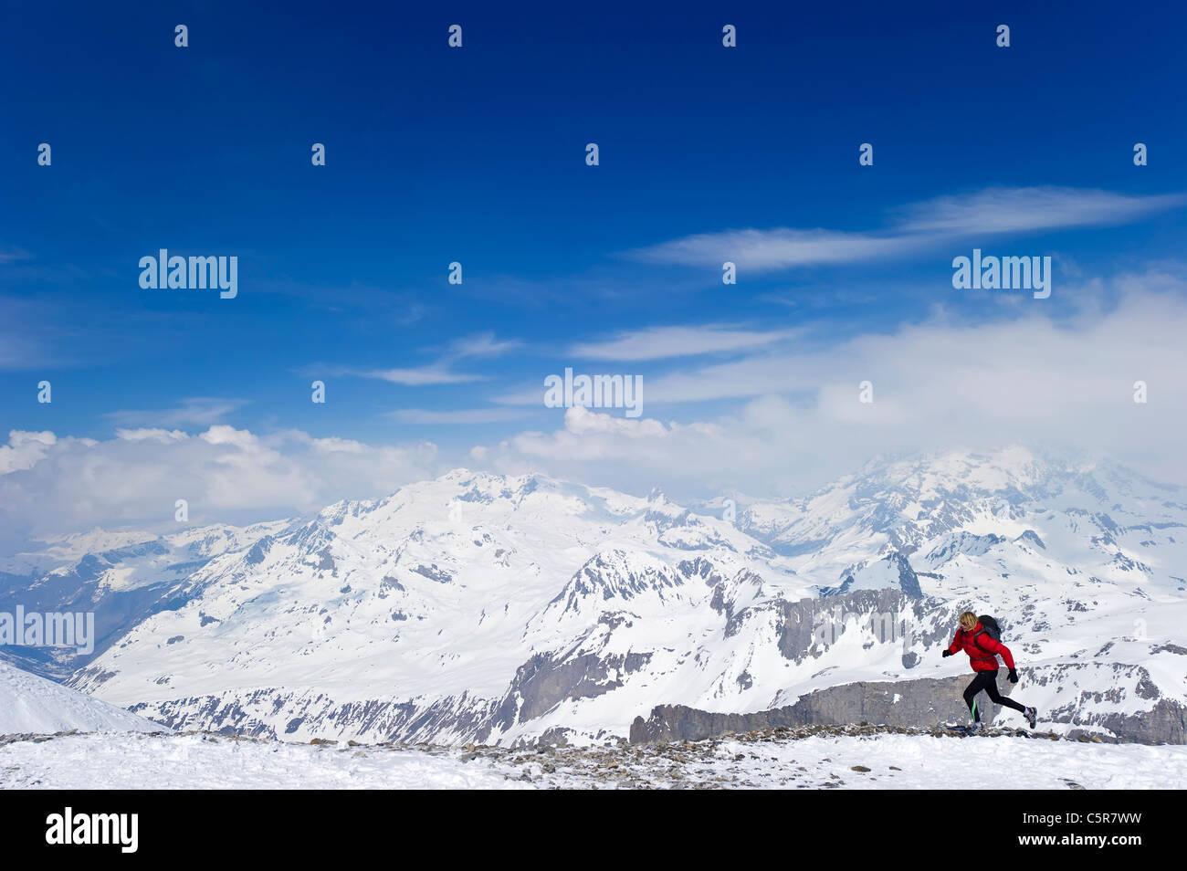 Eine Frau, die auf hohen schneebedeckten Berggipfeln. Stockbild