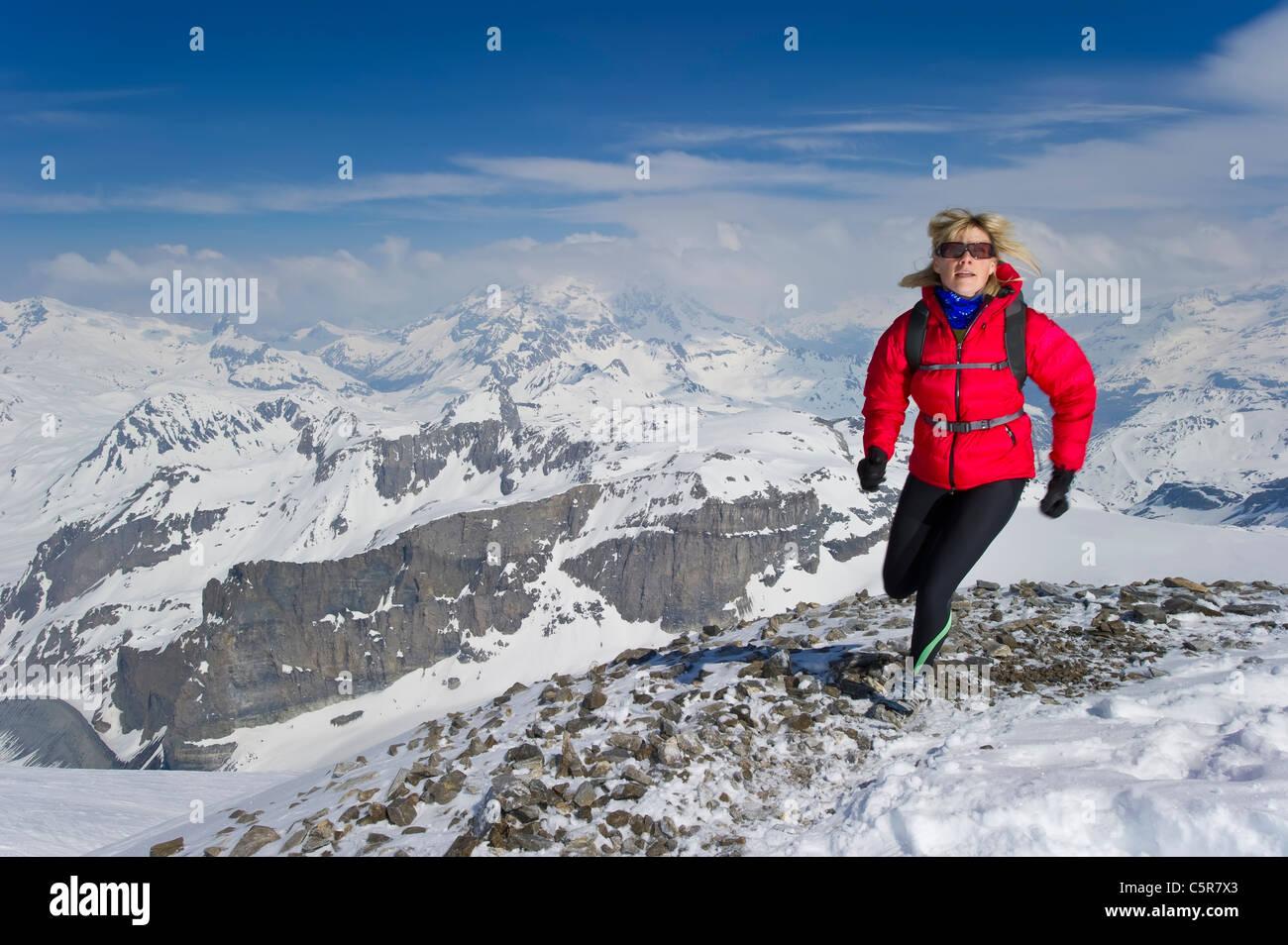 Frau Joggen über hohen schneebedeckten Gipfeln. Stockbild
