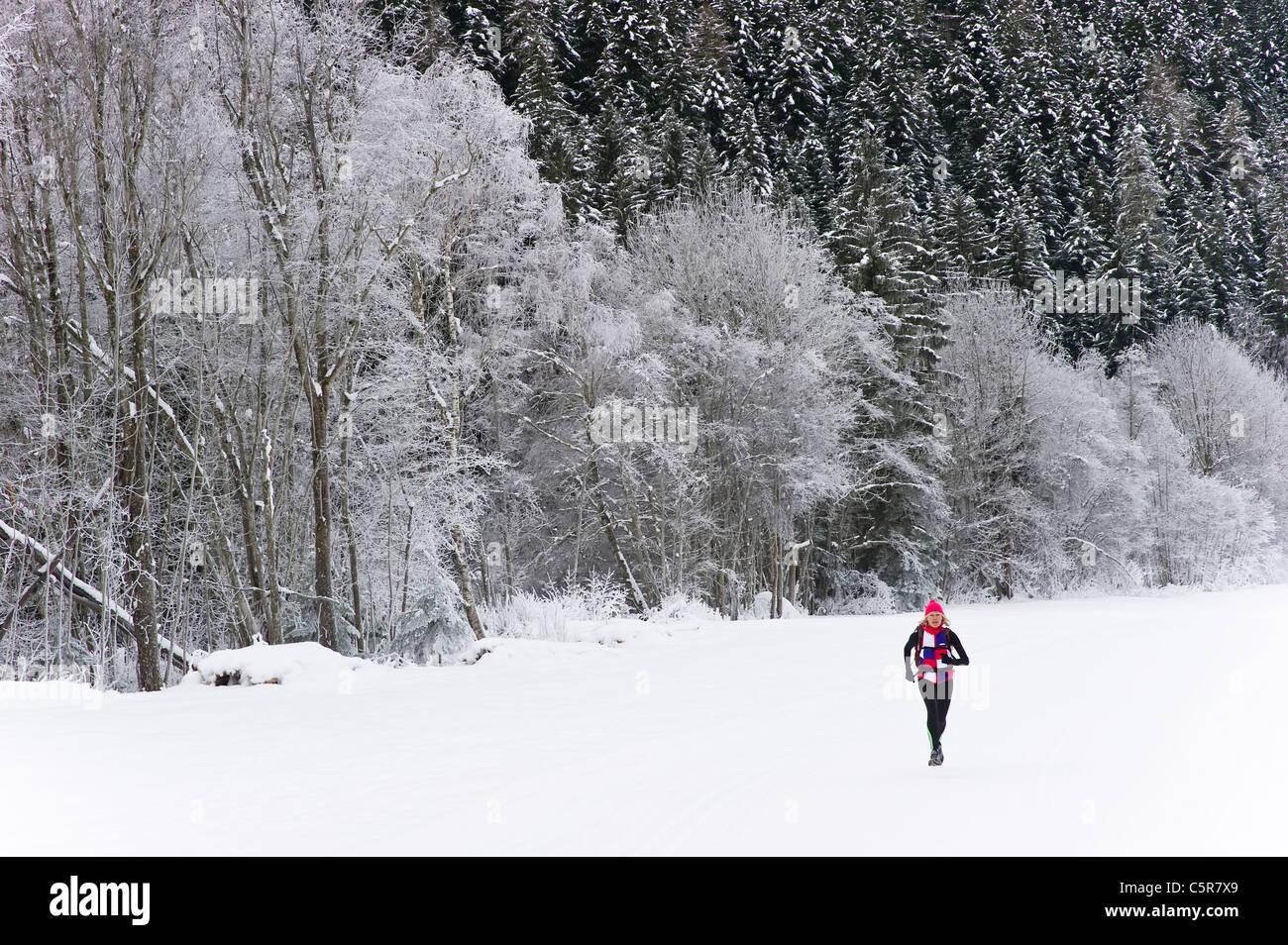 Ein Jogger läuft auf Schneefeld vorbei an schneebedeckten Winterlandschaft. Stockbild