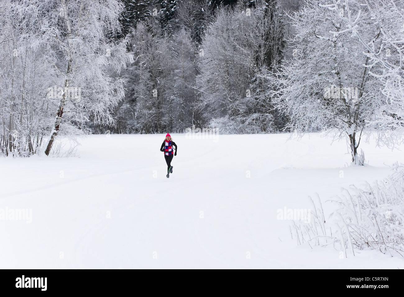 Ein Jogger läuft durch eine tief verschneite Landschaft. Stockbild