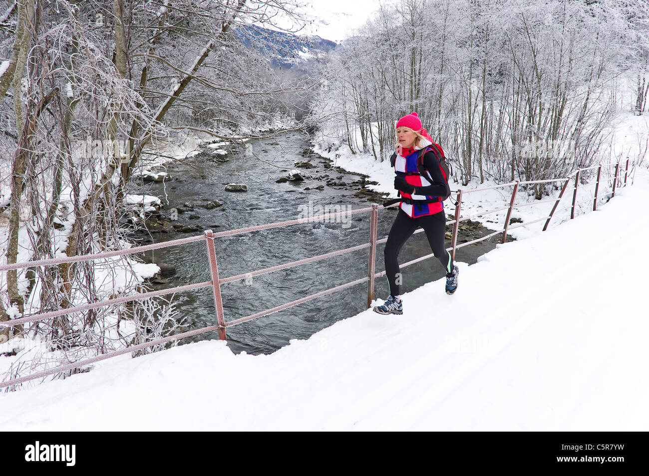 Eine Frau auf einer Brücke über einen schneereichen Winter Fluss joggen. Stockbild