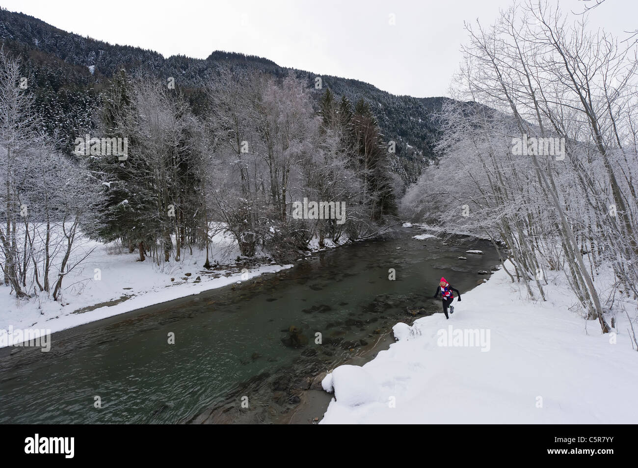 Ein Läufer an einem verschneiten Fluss entlang joggen. Stockbild