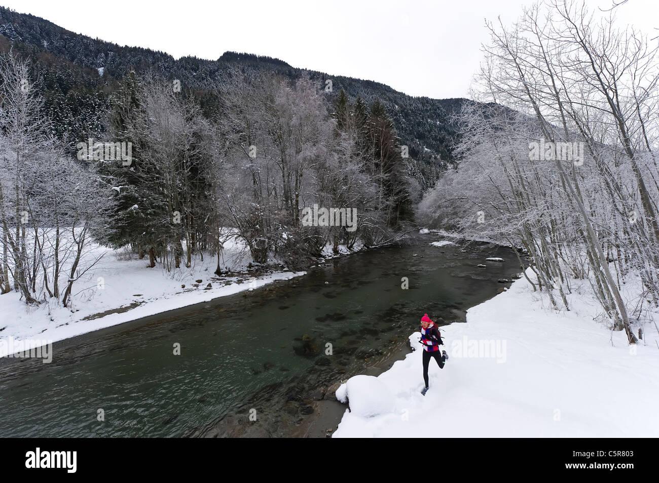Ein Jogger laufen neben einem verschneiten Fluss. Stockbild