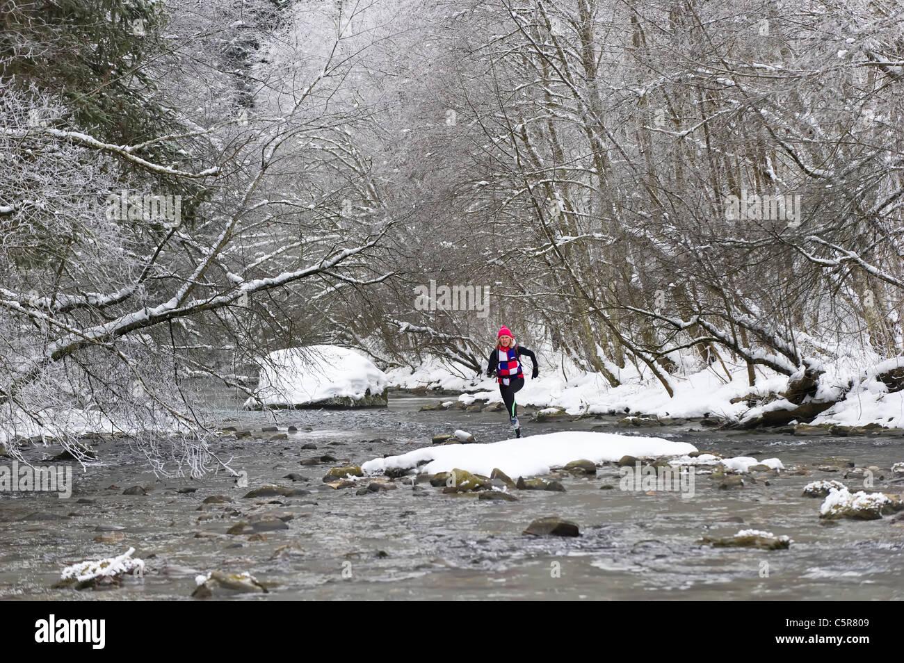 Ein Jogger einen verschneiten alpinen Fluss überquert Stockbild