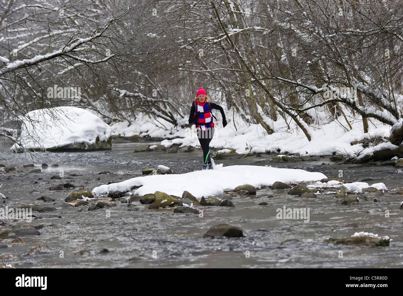 Ein Jogger, einen kalten alpinen Fluss überqueren. Stockbild