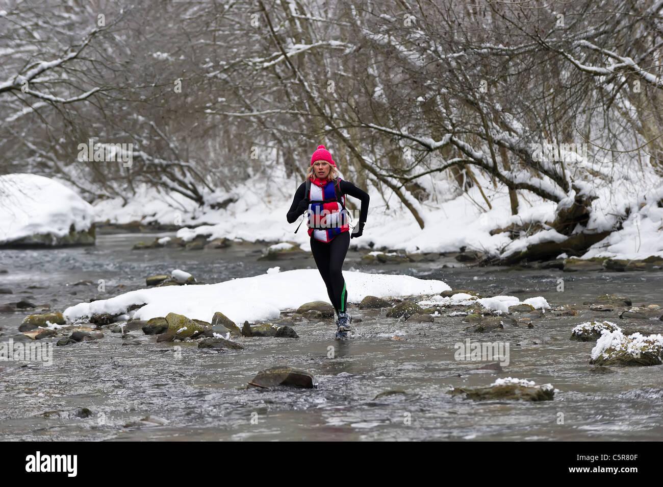 Ein Jogger über einen verschneiten Fluss. Stockbild