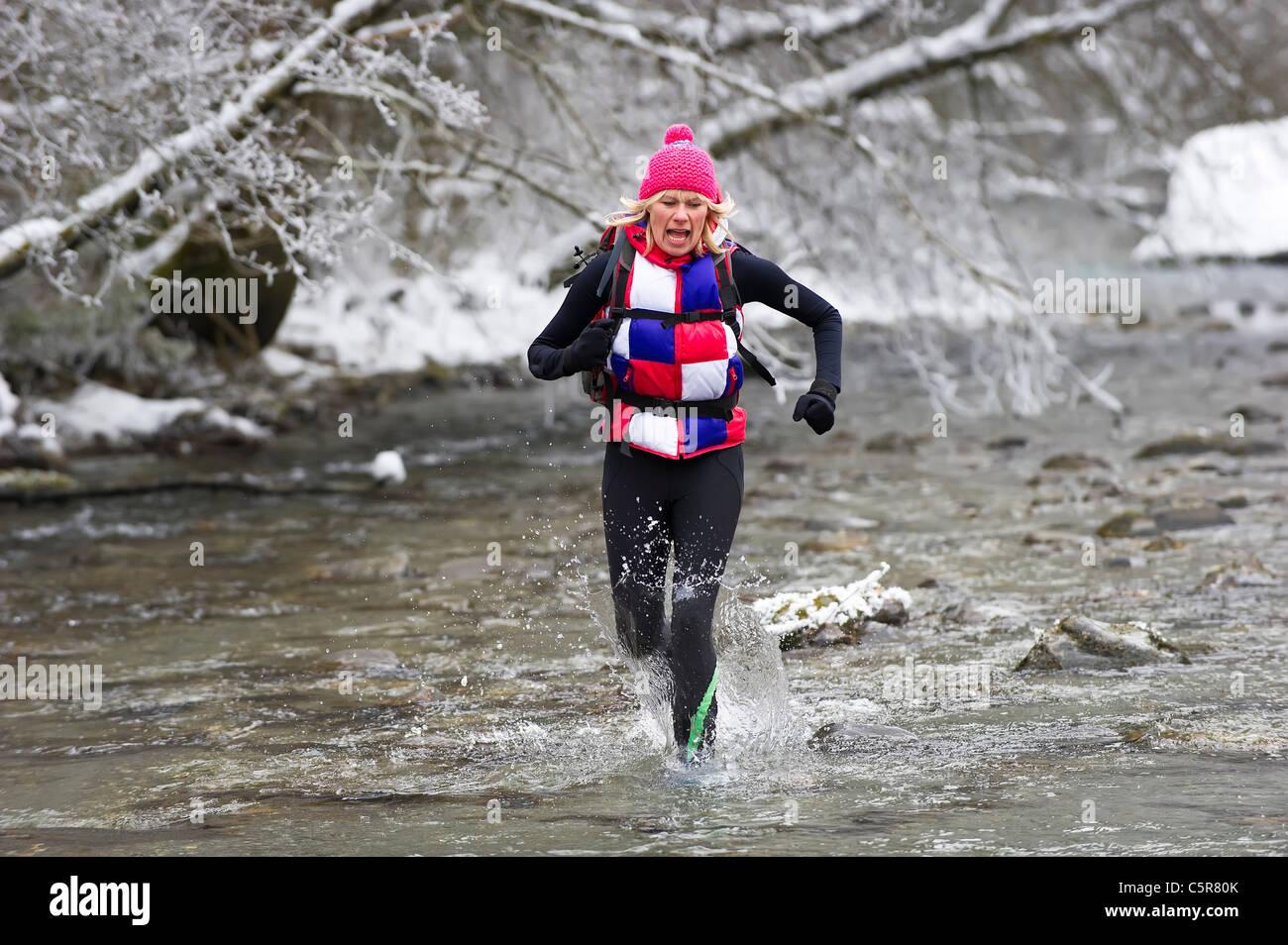 Ein Jogger läuft durch eine verschneite Flussbett und kalten alpinen Gewässern. Stockbild