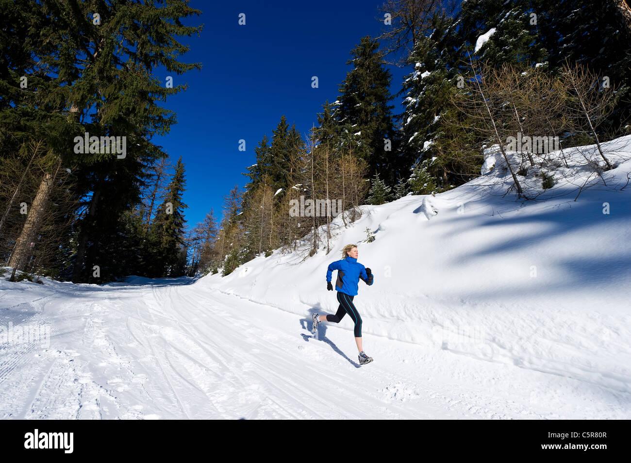 Ein Jogger läuft durch einen alpinen Wald. Stockbild