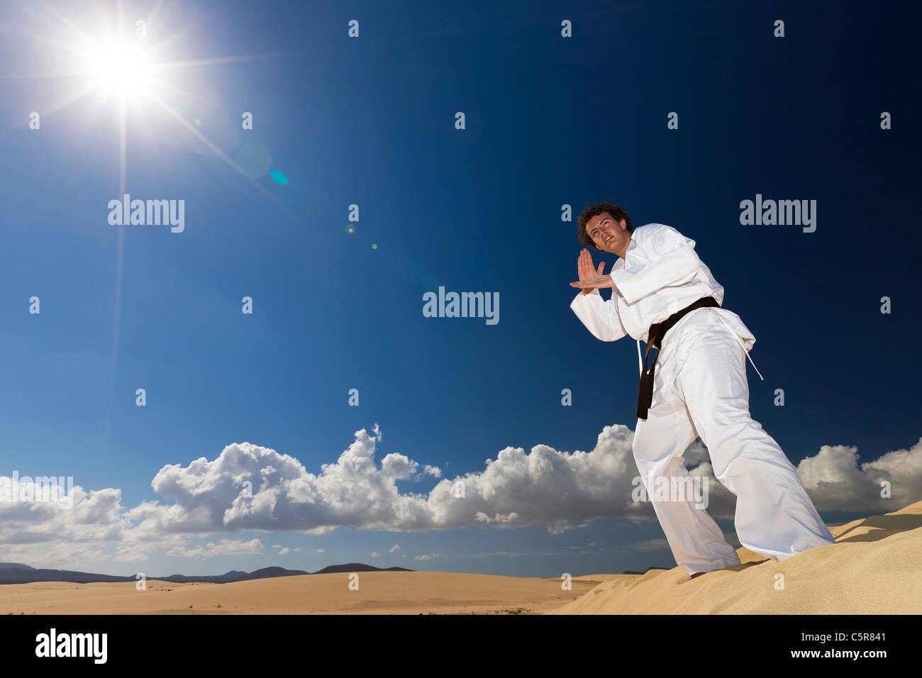 Schwarzgurt martial arts training auf Dünen der Wüste. Stockbild