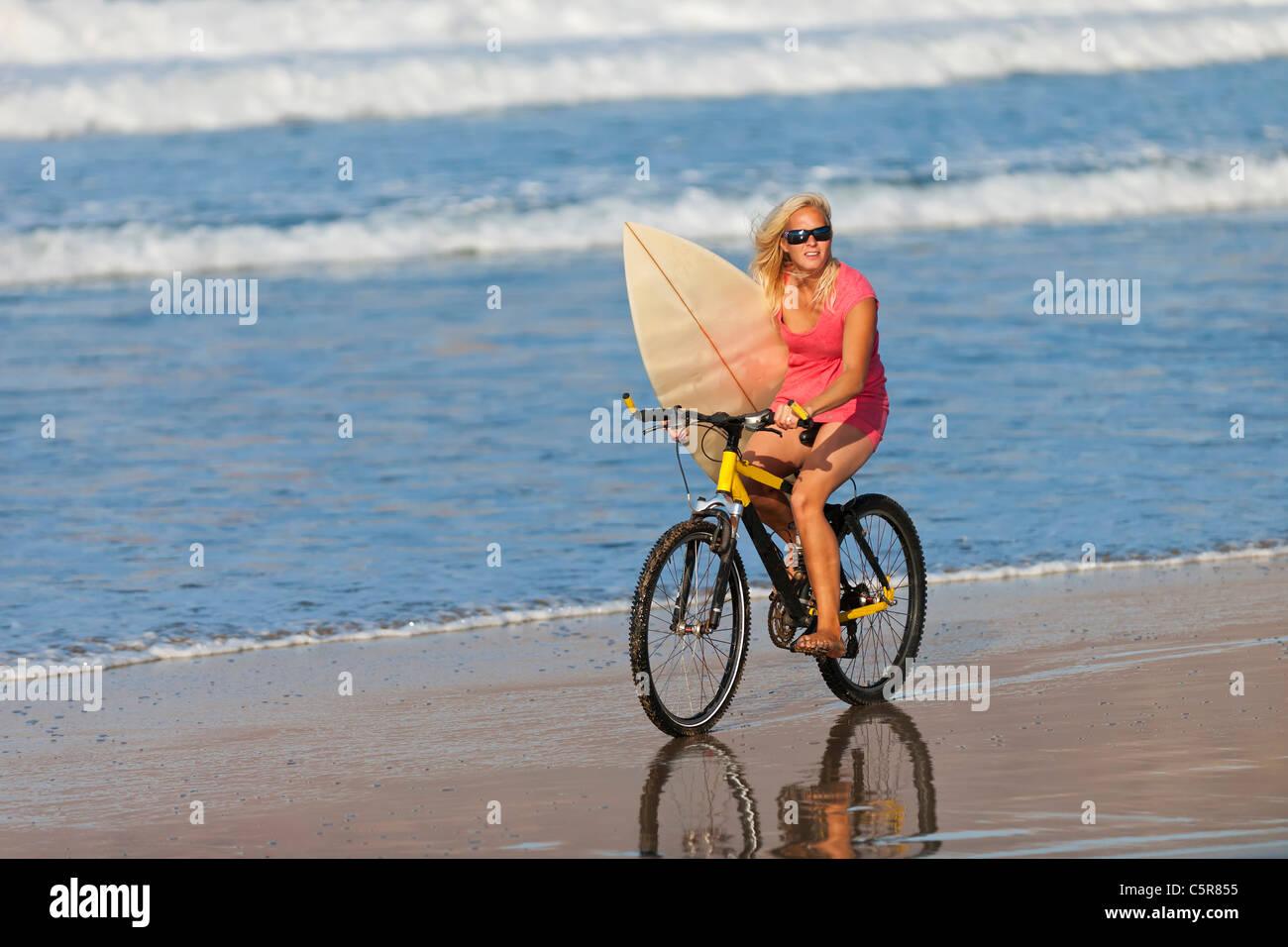 Ein Surfer auf einem Mountainbike in den Ozean. Stockbild