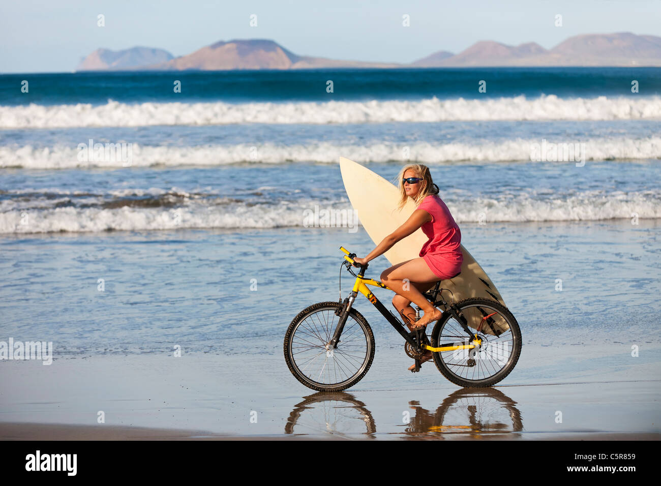 Surfer reiten Mountainbike entlang der Ozeane. Stockbild