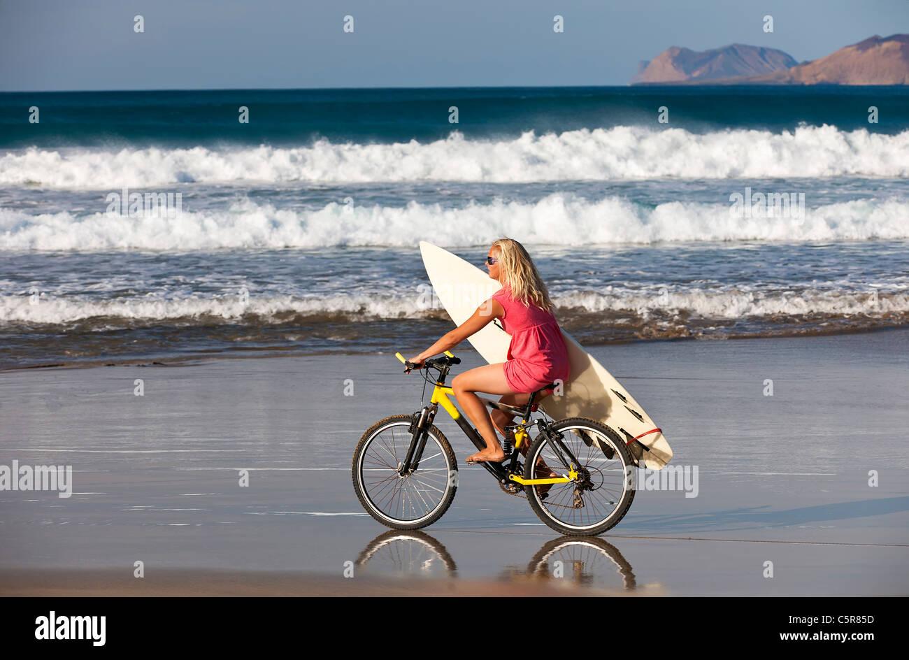 Surfer Mädchen reitet auf den Wellen des Ozeans auf Mountainbike. Stockbild