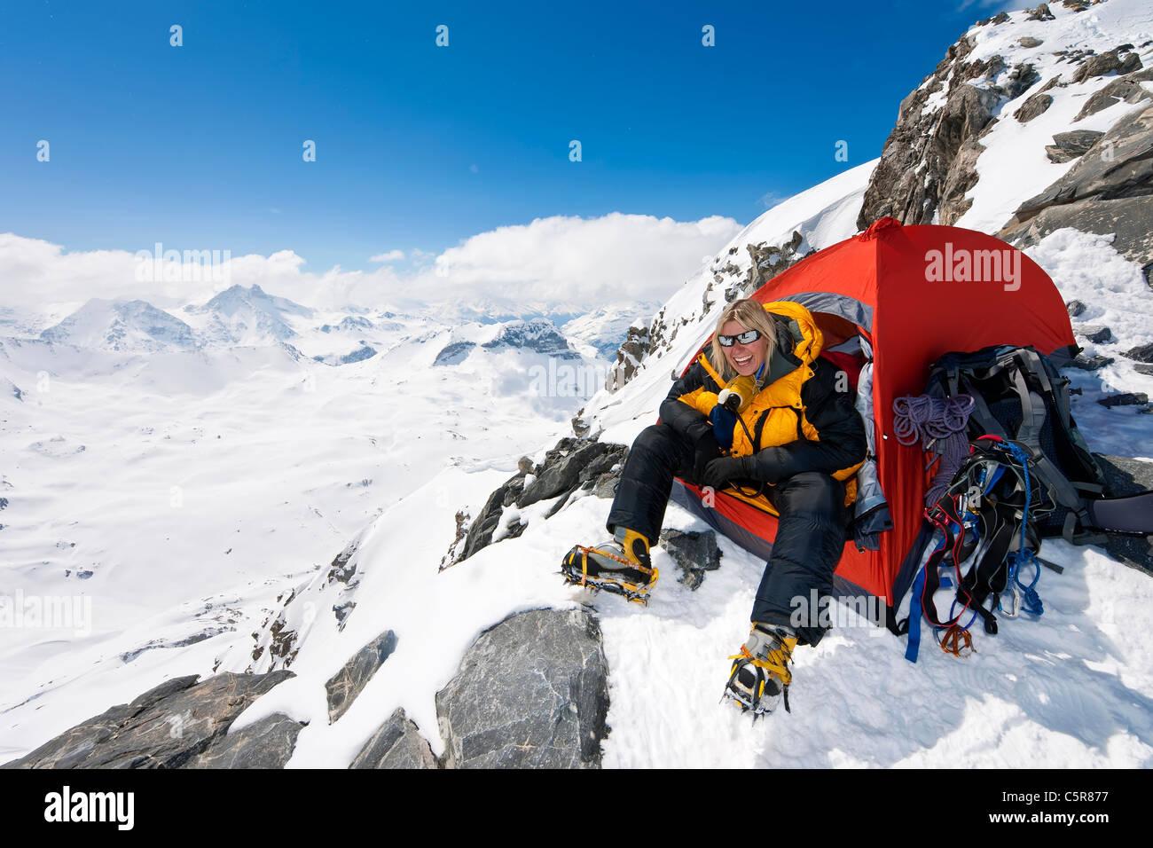 Ein glücklich Bergsteiger sitzen in der Tür von ihrem Zelt Stockbild