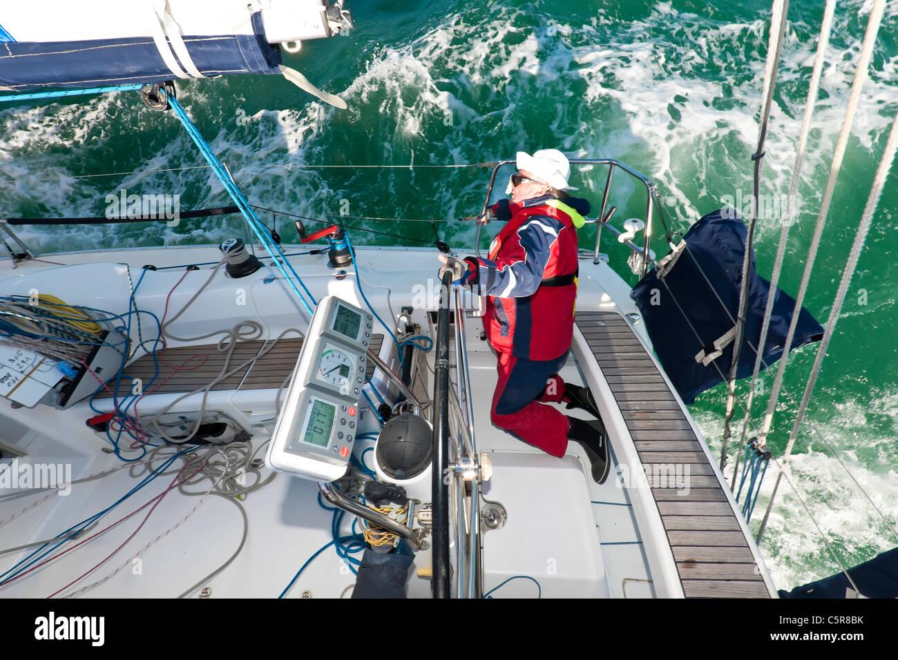 Der Kapitän, die Lenkung eines Ozeans abgehackt Meereswellen Yacht im Rennen los. Stockbild