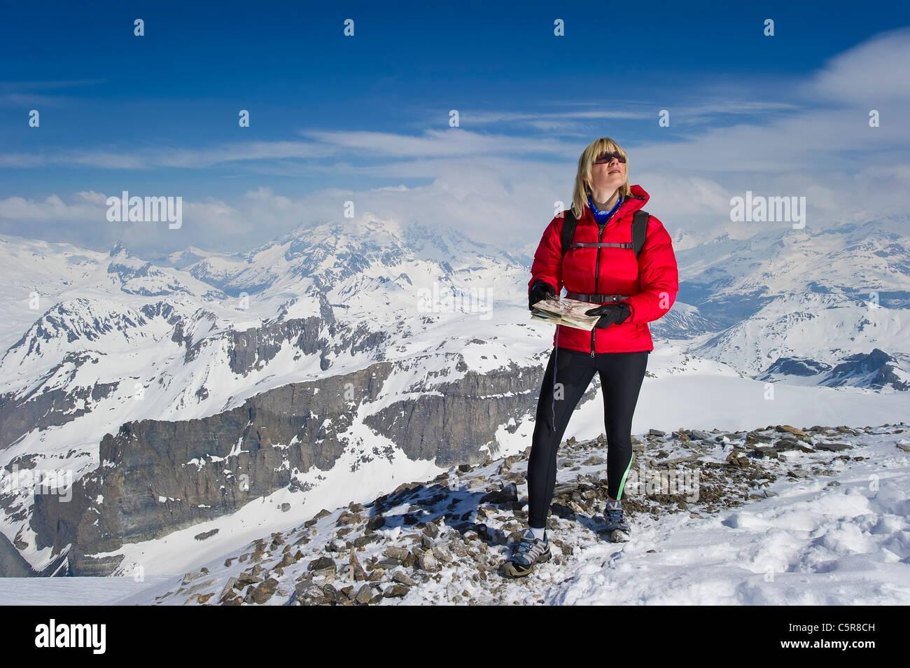 Eine Frau im verschneiten Hochgebirge mit Karte und Kompass für Orientierungslauf. Stockbild