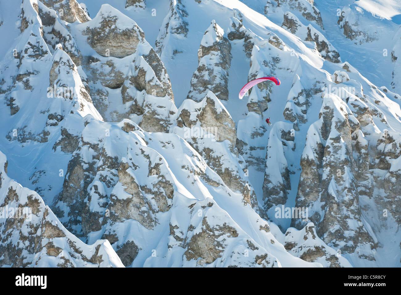 Ein Gleitschirmflieger eine beeindruckende Felsformation Berg vorbeifliegen. Stockbild