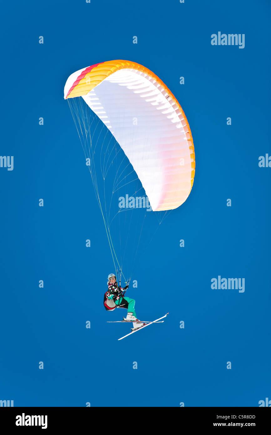 Eine weibliche Gleitschirm pilot lächelt wie sie fliegen, ist ihre Flügel. Stockbild