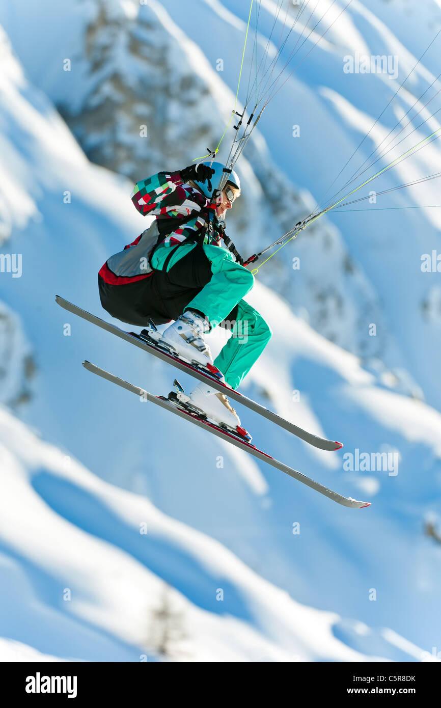 Ein Gleitschirm Pilot ihr Fliegenflügel vorbei an schneebedeckten Bergen. Stockbild