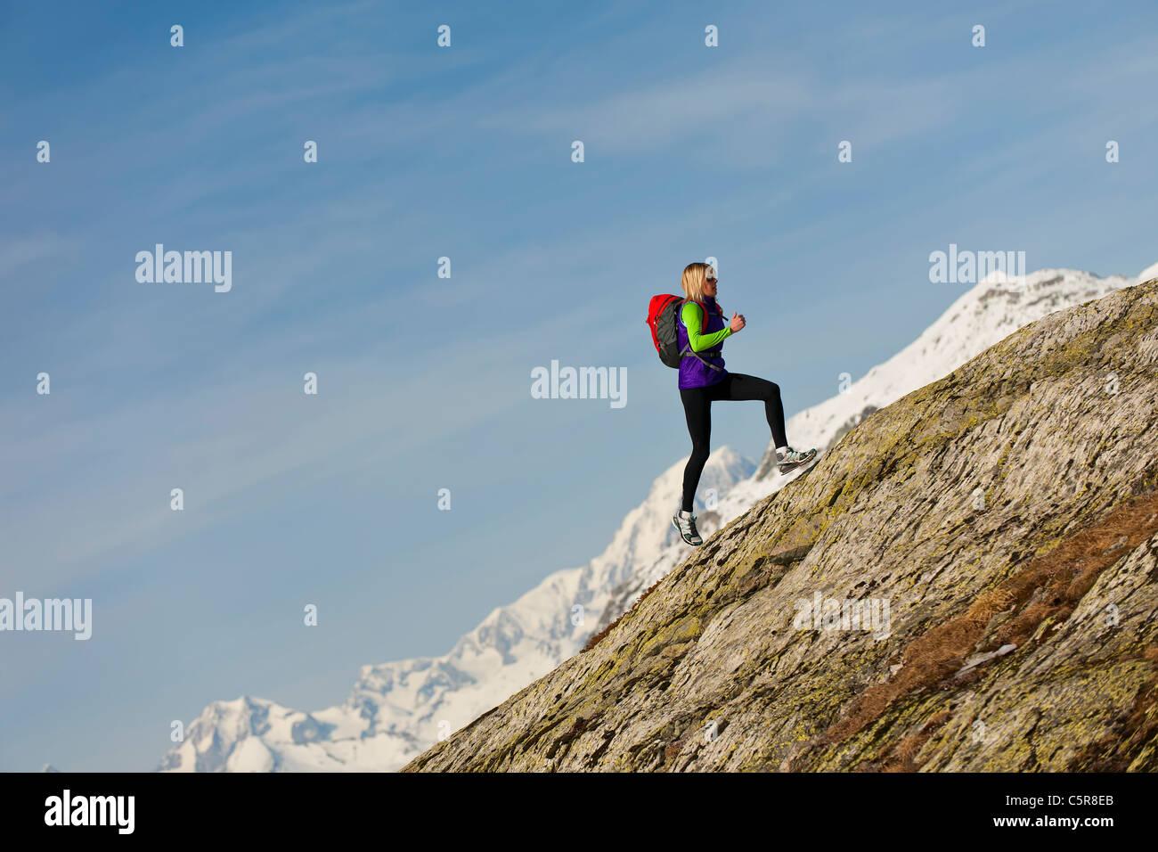 Ein Läufer läuft auf einer steilen Felswand in großer Höhe. Stockbild