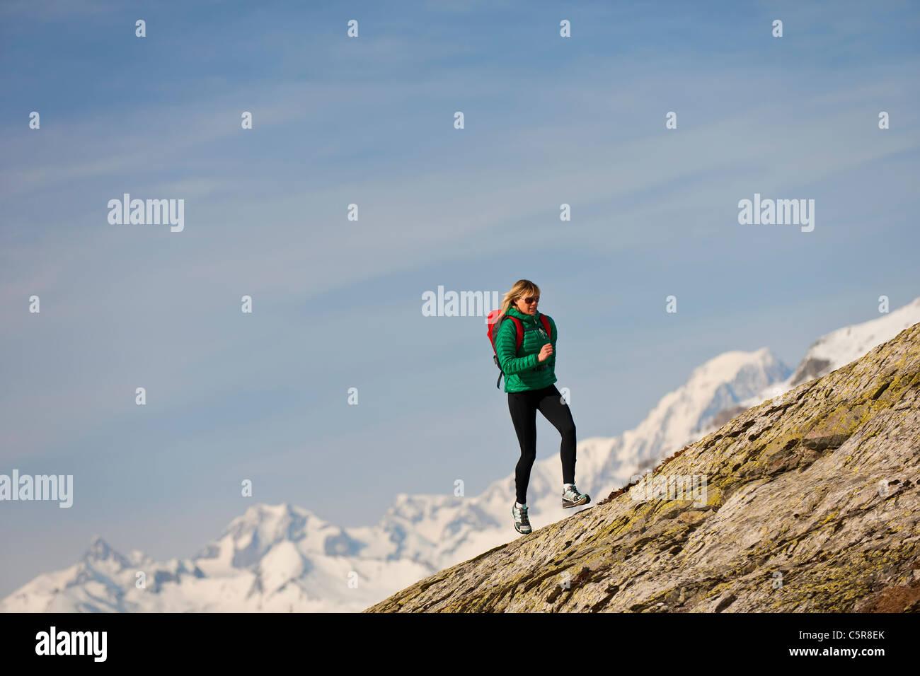 Ein Läufer läuft über einen felsigen Berg. Stockbild