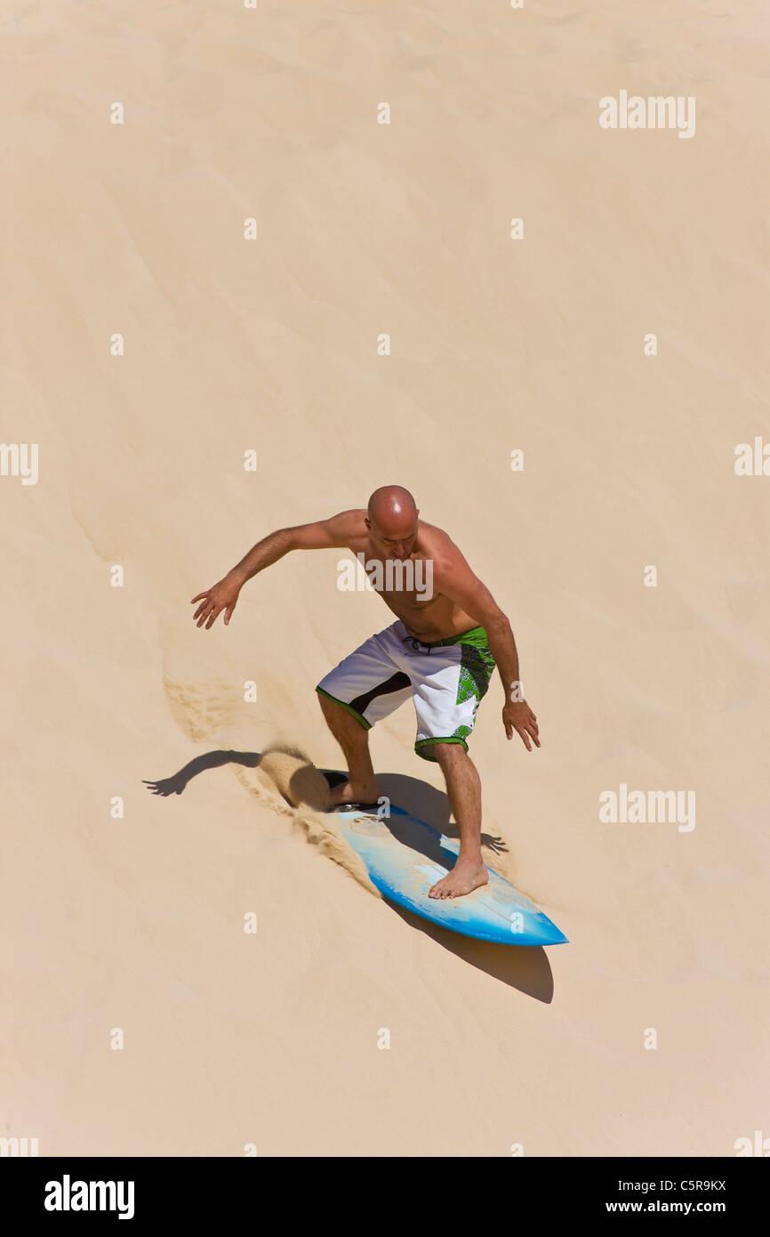 Surfer reiten Sanddüne. Stockbild