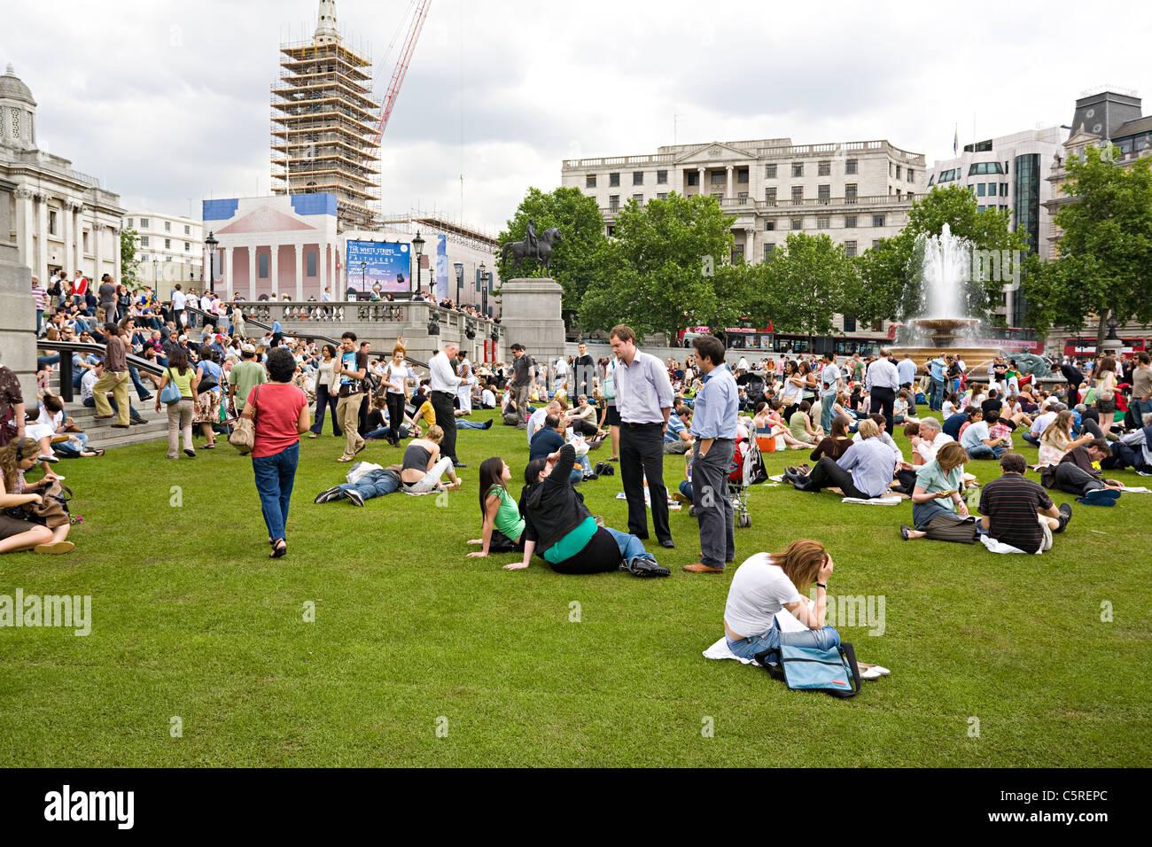 Menschen auf dem Rasen am Trafalgar Square London Vereinigtes Königreich Stockbild