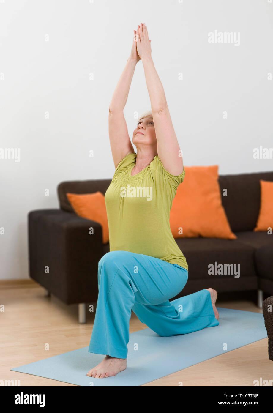 Deutschland, Düsseldorf, Frau Yoga in der Nähe von Sofa zu Hause machen Stockbild