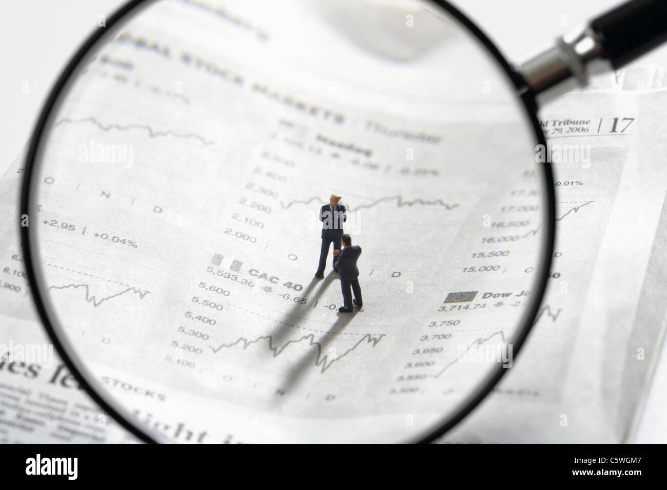 Zwei Figuren auf Zeitungspapier stock Quotes mit Lupe Linse im Vordergrund Stockbild