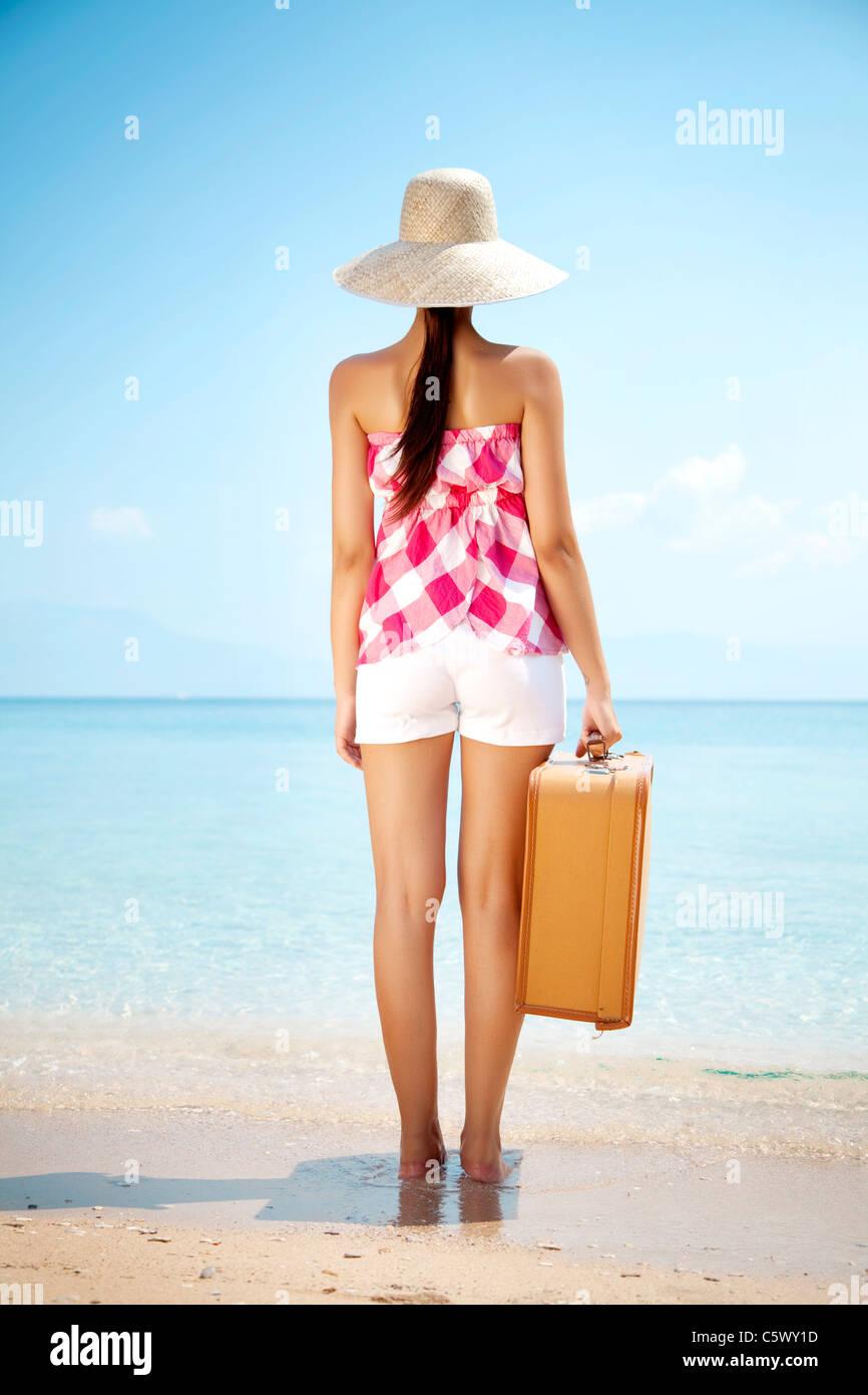junge Frauen stehen am Strand mit Vintage Koffer Stockbild