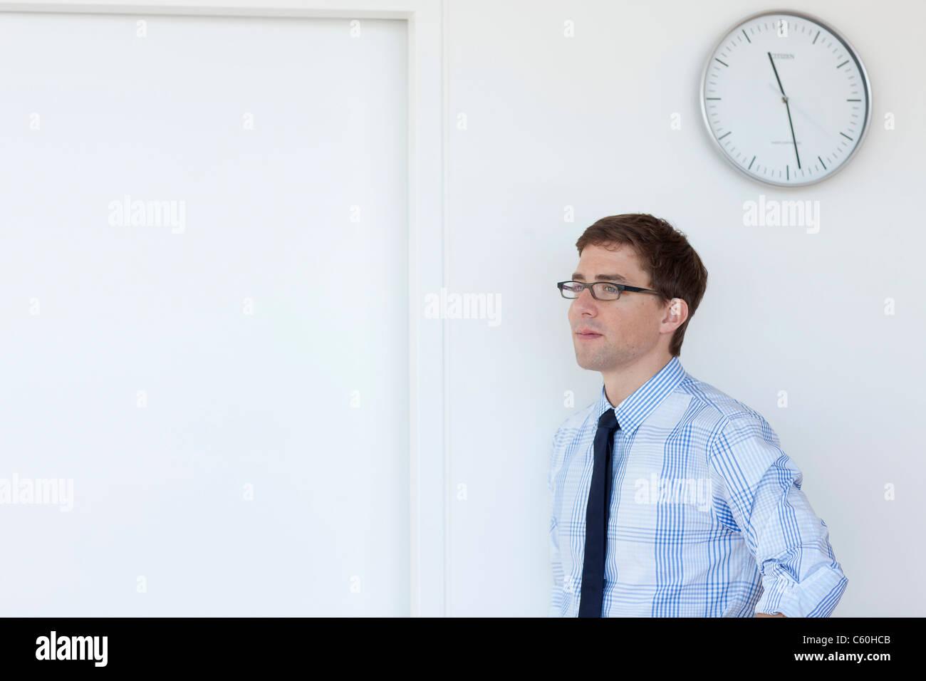 Geschäftsmann, stehen unter Büro-Uhr Stockbild