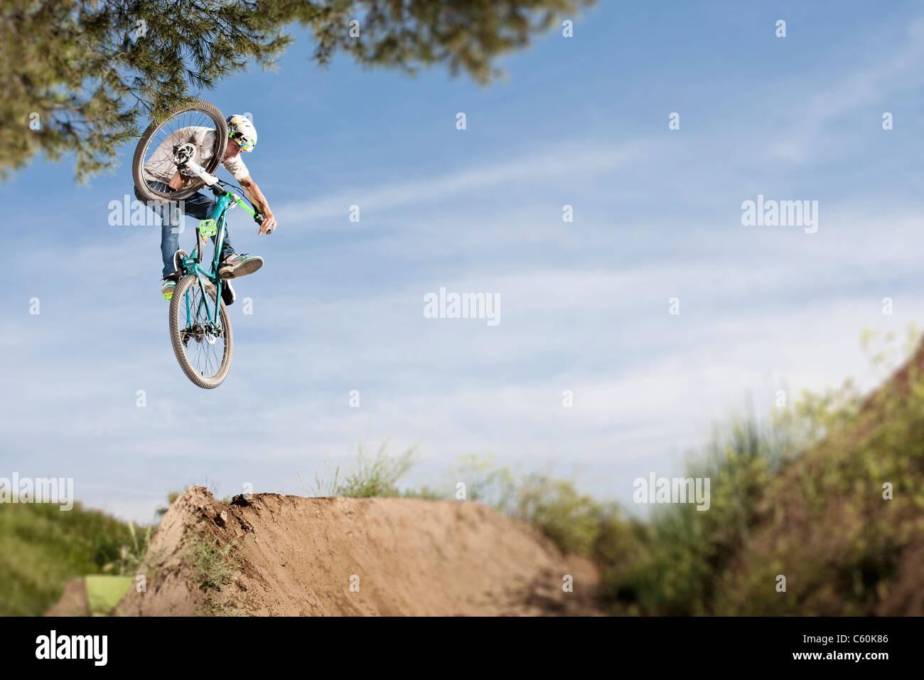 Schmutz-Biker machen Tricks bei Sprung Stockbild