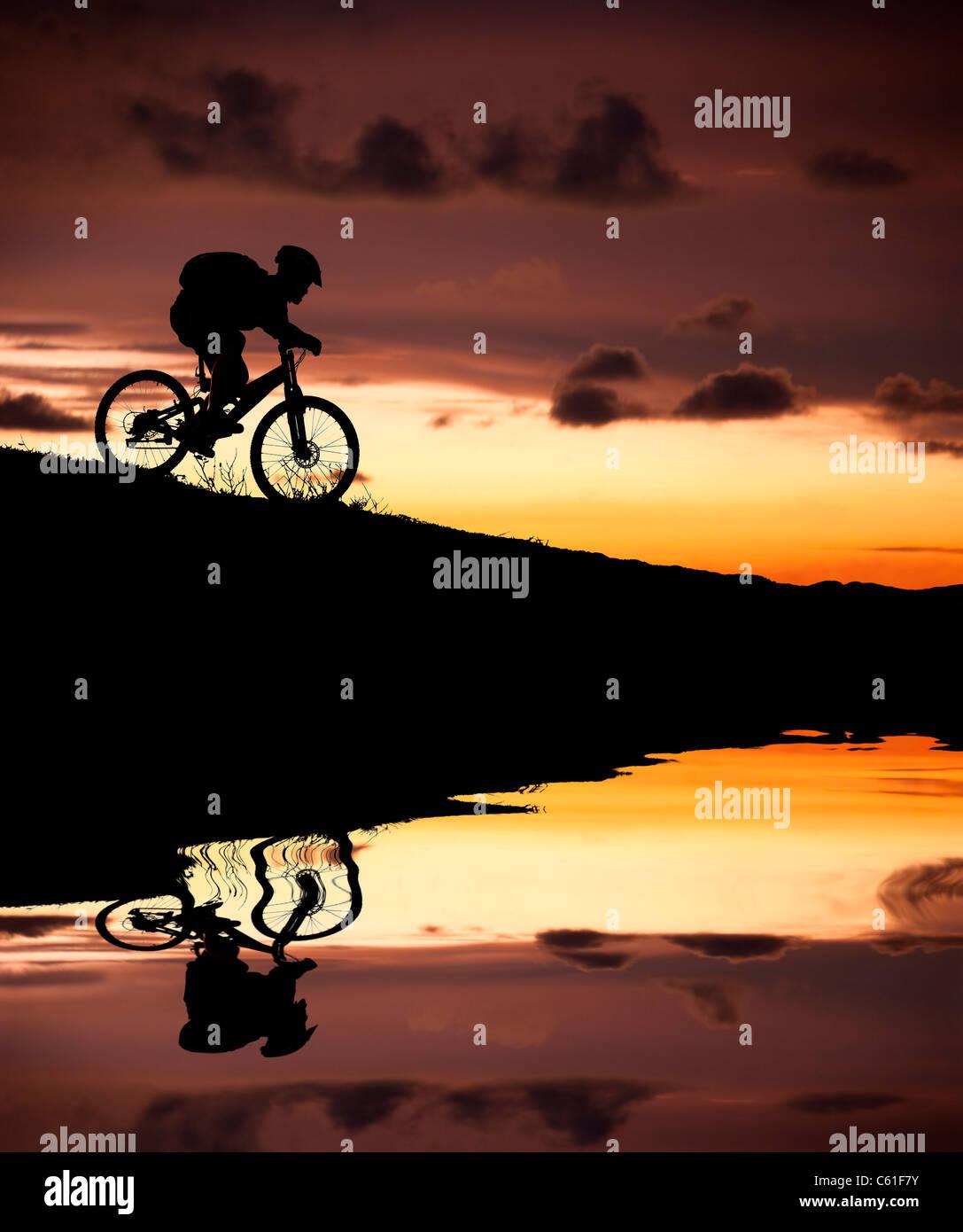 Silhouette der Mountainbiker mit Reflexion und Sonnenuntergang Stockbild