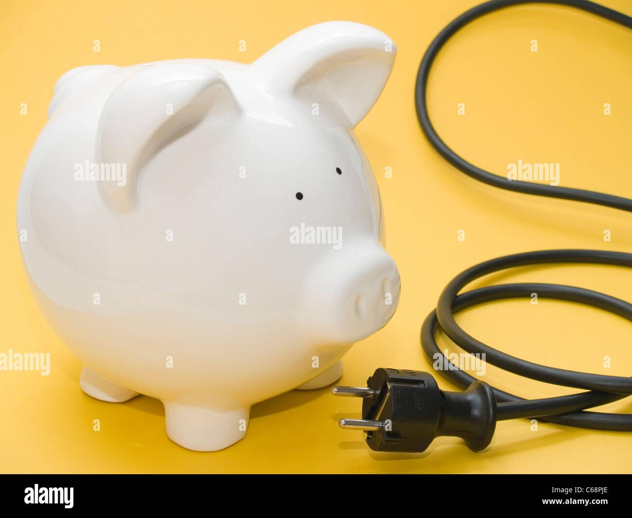 Sparschwein und Elektrokabel Stockbild