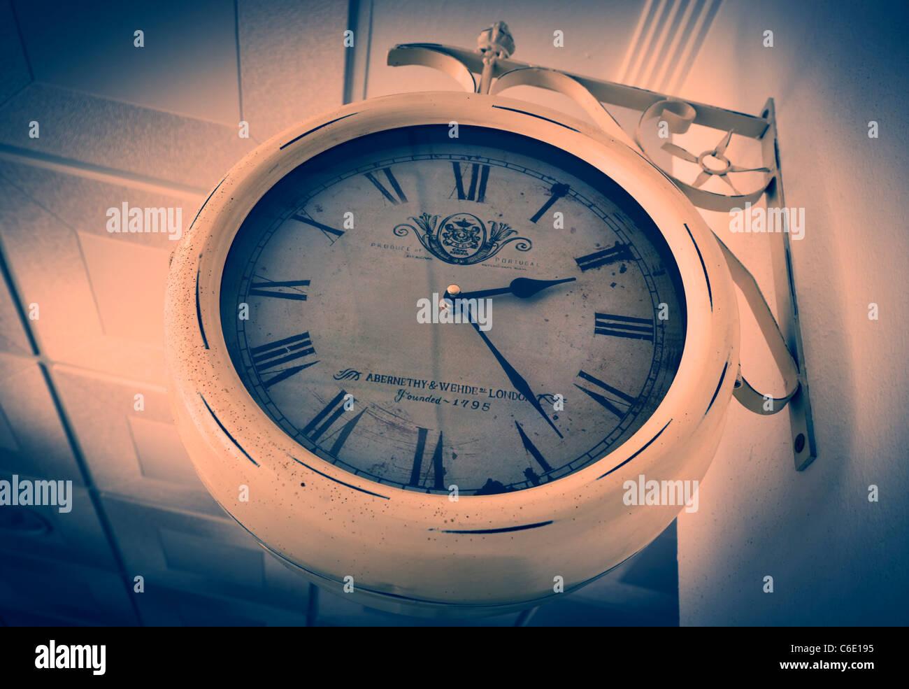 Alte Uhr mit römischen Ziffern auf Wand. Stockbild