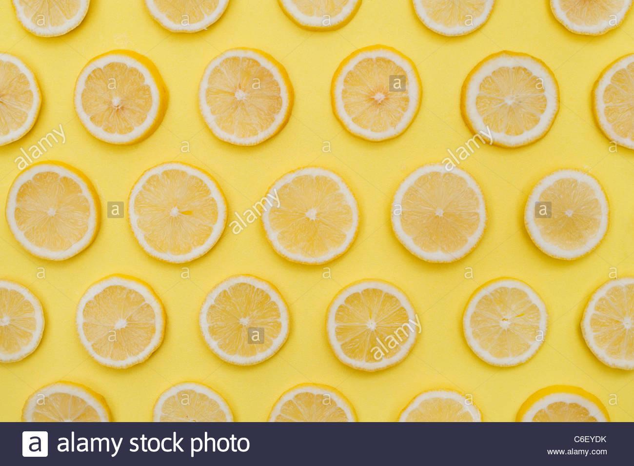 Citrus x Limon. Zitronenscheiben Frucht auf gelbem Hintergrund. Essen-Muster Stockbild