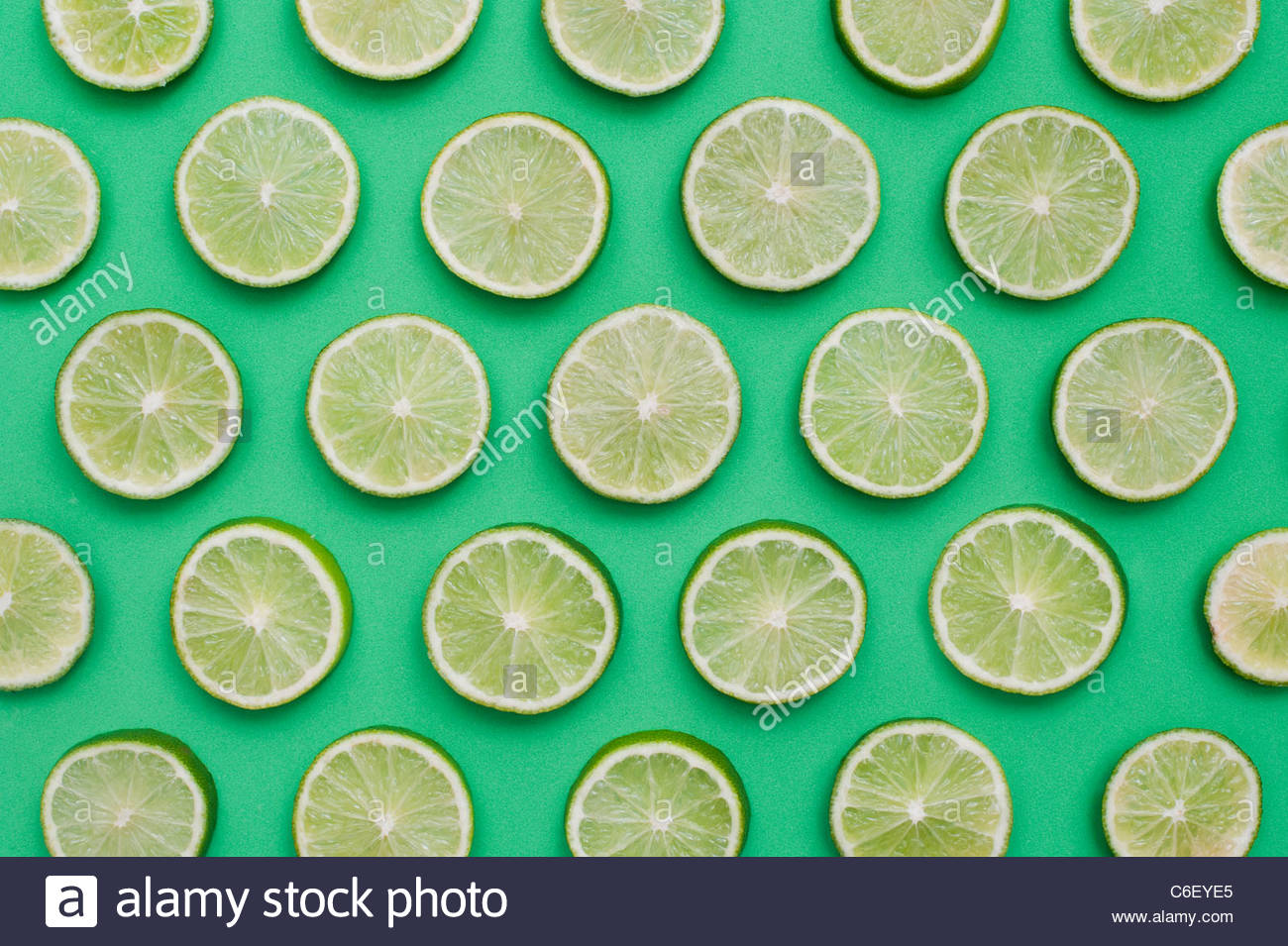 Citrus x Sinensis. Lime FRUCHTSCHEIBEN auf grünem Hintergrund. Essen-Muster Stockbild
