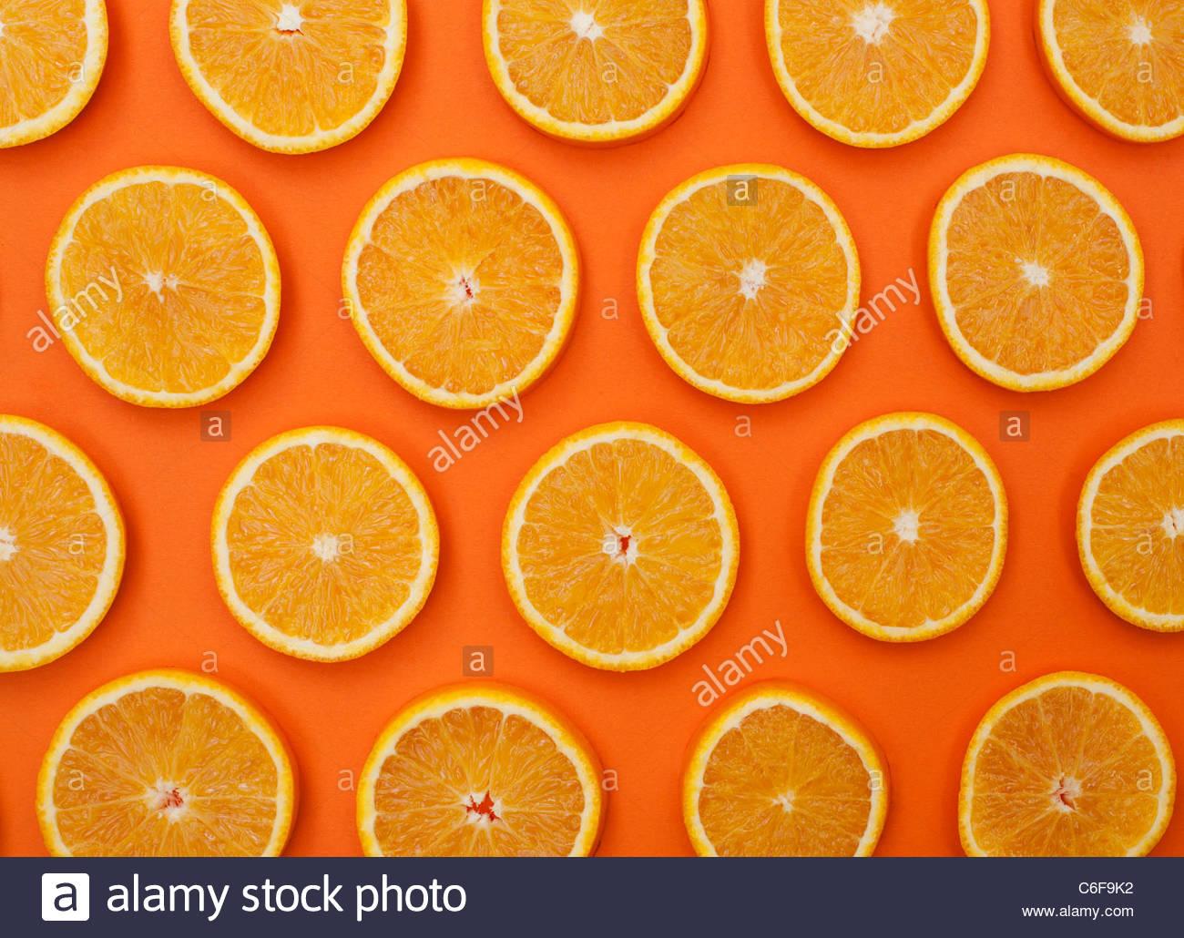 Citrus x Sinensis. Orange FRUCHTSCHEIBEN auf orangem Hintergrund. Essen-Muster Stockbild