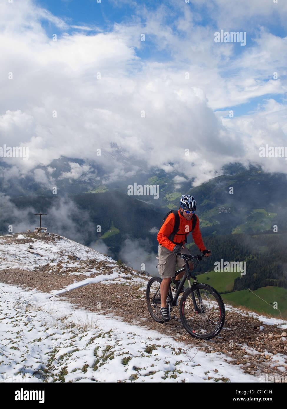 Ein Mountainbiker kommt auf dem Gipfel des Kronplatz, Berge, ein Kreuz und Wolken im Hintergrund. Stockbild