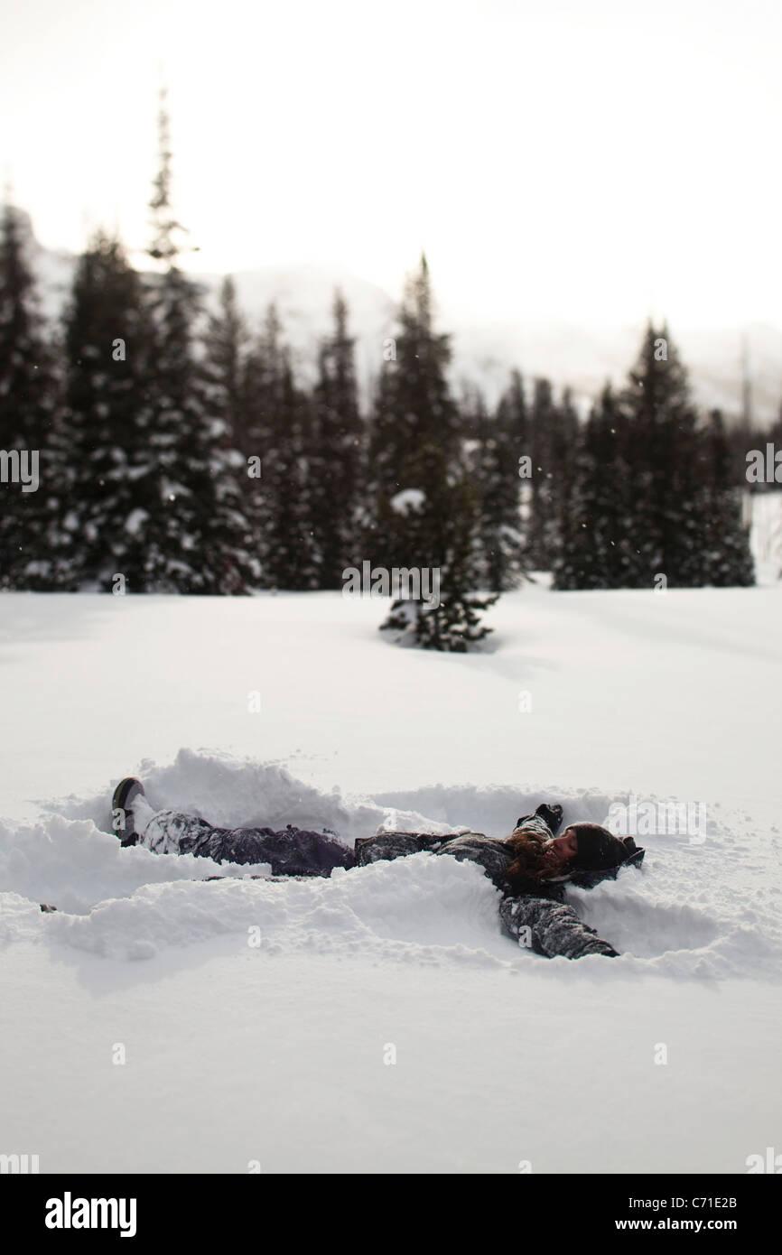 Eine schöne Frauen Lächeln bei der Herstellung eines Schneeengel auf einem unberührten Gebiet bei Stockbild