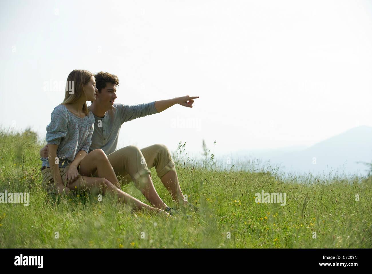 Paar, sitzen auf der Wiese, Mann zeigte auf Distanz Stockbild