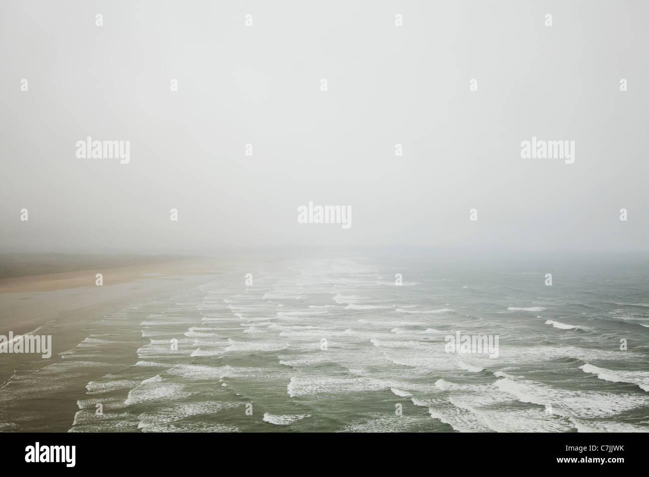 Wellen am Strand von Nebel Stockbild