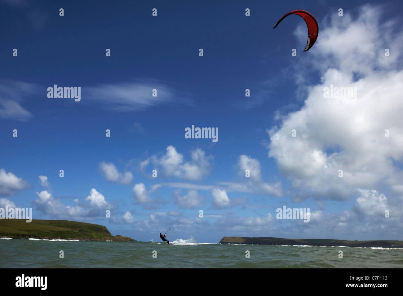 Kitesurfer auf dem Wasser unter blauem Himmel Stockbild