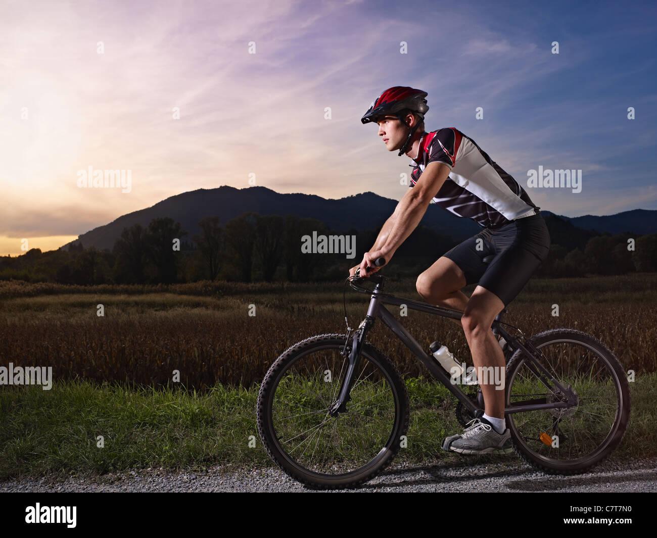 sportlichen Aktivität: jungen Erwachsenen Radfahrer fahren Mountainbike in der Natur. Horizontale Form, Seitenansicht, Stockbild